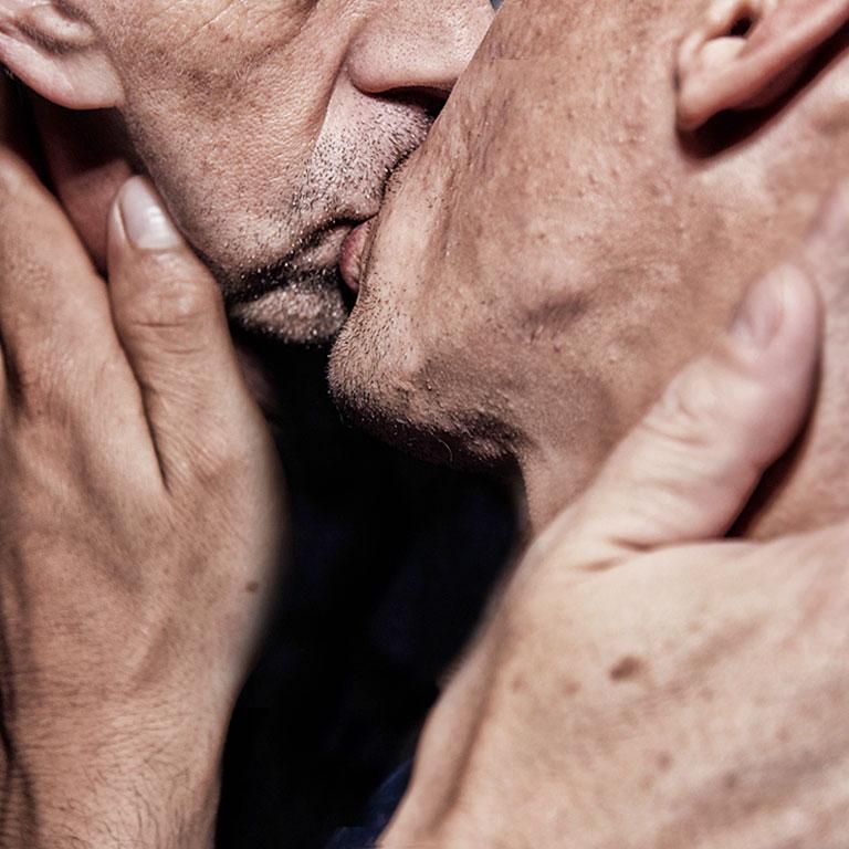 Two older men kissing