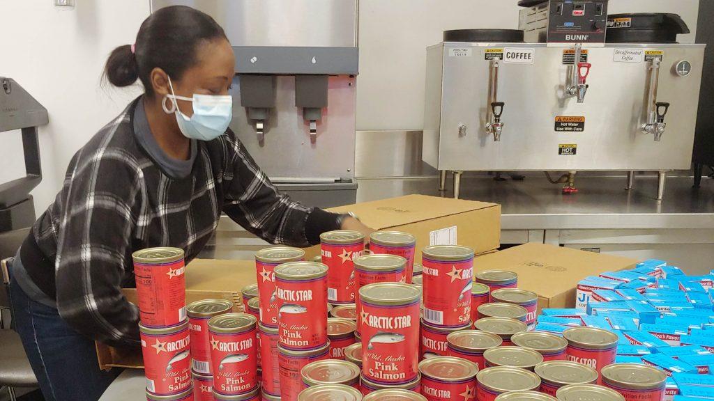 GMHC volunteer preparing food packages for clients.