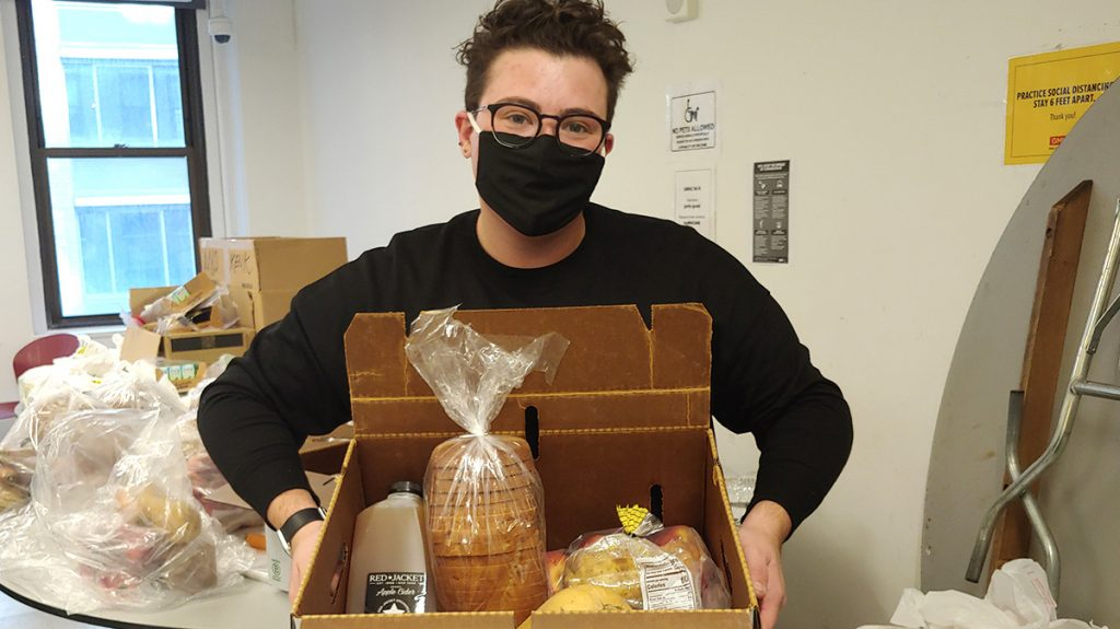 GMHC staff member preparing a box meal for an agency client.